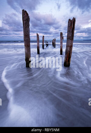 Scenic view of wooden poles on a beach, the movement of the waves is shown in addition to a colorful evening sky - Location: Baltic Sea, Rügen Island - Stock Photo