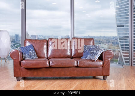 brown armchair against the backdrop of a huge window view from the panoramic windows. - Stock Photo