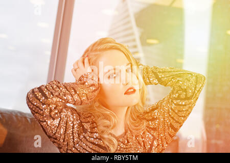 young beautiful blonde woman sits on a leather sofa against the background of a panoramic window overlooking the skyscrapers and a big city. - Stock Photo