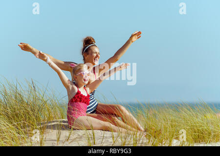happy modern mother and child in beachwear on the seashore looking into the distance and rejoicing. stressed free beach retreat.. Hair healthy conditi - Stock Photo