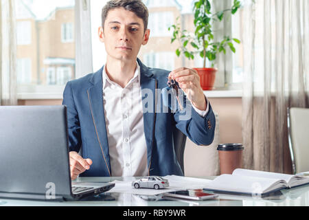 Man agent holding car keys and documents for registration of the car in the office. The concept of buying selling and rental of transport - Stock Photo