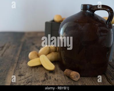 vintage moonshine jug on a rustic wooden table with potatoes and corn cob cork for distilling hard liquor - Stock Photo