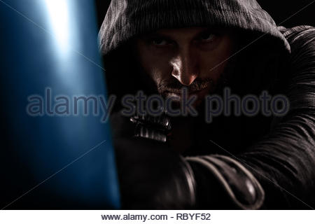Studio shot of male boxer punching a boxing bag. - Stock Photo