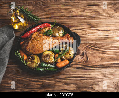 Roasted turkey leg with vegetables, carrots, peppers, potatoes vegetables in frying pan - Stock Photo