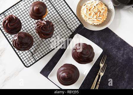Chocolate glazed cupcakes and toasted meringue tart on table. - Stock Photo