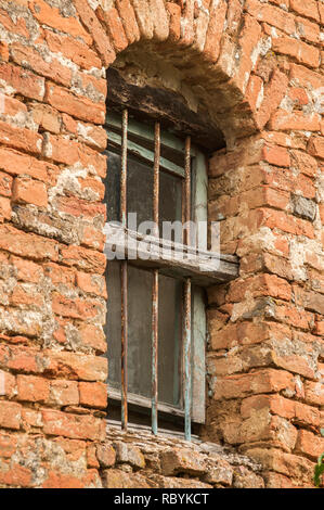 Grunge broken  window of old rural weathered neglected abandoned house red brick wall closeup - Stock Photo