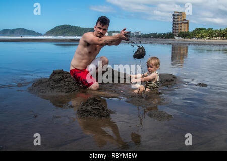 A photo of father and son digging a hole at the beautiful beach of Jaco, Costa Rica - Stock Photo