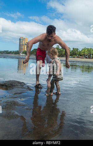 A photo of father and son dancing at the beautiful but empty beach of Jaco, Costa Rica - Stock Photo