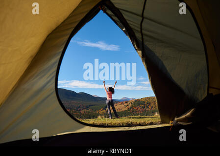View from inside of tourist tent in mountains. Slim sportive dark-haired young woman standing on grassy valley with her hands up on background of dist - Stock Photo