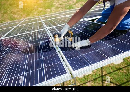 using powerful modern drill, mounter installing solar panels on roof. Ecological, environmental friendly technologies exploiting renewable solar energ - Stock Photo