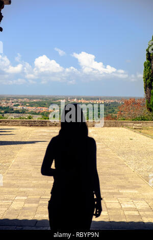 A beautiful woman is standing in the doorway of the basilica of Sant'Angelo in Formis.  She overlooks the valley of Capua, or does she look inside? - Stock Photo