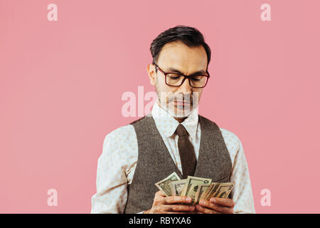 Mature man counting money, isolated on pink studio background  - Stock Photo