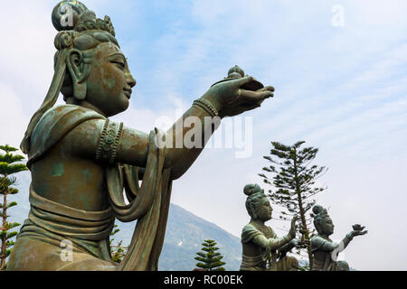 Statues of Buddhist saints making offerings to Buddha at the Tian Tan Buddha, Lantau Island, Hong Kong - Stock Photo