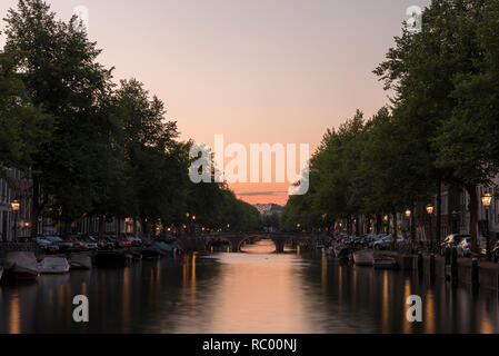 Sunset, looking down a canal in Amsterdam. The sky is orange and the street lights reflect on the calm water - Stock Photo