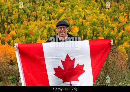 A man photographs the coastline at Forillon National Park on the Gaspé Peninsual of Quebec, Canada. He uses a mobile phone. - Stock Photo