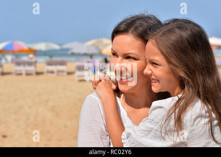 Portrait of mother with daughter on beach - Stock Photo