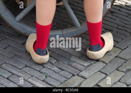 Back view of classic Dutch wooden shoes worn by a girl with red socks - Stock Photo