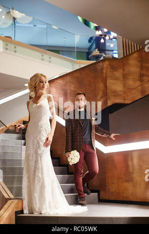 Bride in a chic long dress with a train and the groom stand on big stairs, couple in love hugs on stairs kiss and look at each other. Day of the weddi - Stock Photo