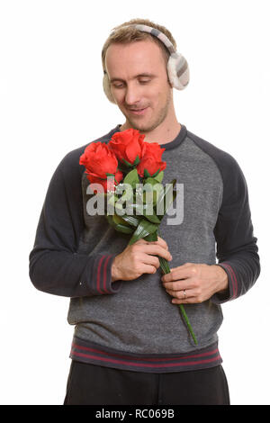 Handsome Caucasian man holding red roses ready for Valentine's d - Stock Photo