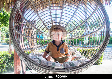 A portrait of a young boy with a hat happily sitting in a nice garden swing chair - Stock Photo