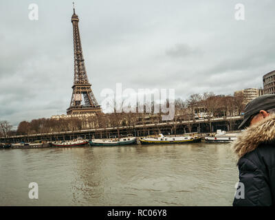 PARIS, FRANCE - JAN 30, 2018: Parisian senior man watch the swollen river Seine near the Eiffel Tower as the river's embankments overflow after days of heavy rain - Stock Photo