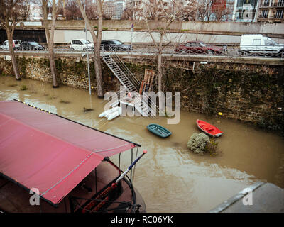 PARIS, FRANCE - JAN 30, 2018: Swollen river Seine river's embankments overflow after days of heavy rain - boas used for people living on the Peniche barges - Stock Photo