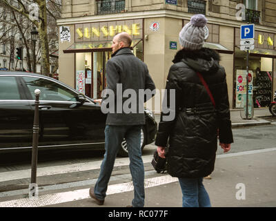 PARIS, FRANCE - JAN 30, 2018: Daily Paris scene with french male and female crossing street in front of Mercedes -Benz luxury limousine in Paris, on the Rue St Vincent de Paul - Stock Photo