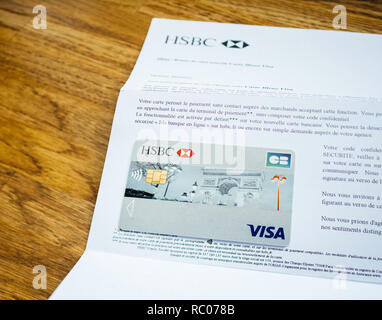 PARIS, FRANCE - JAN 26, 2017: New Contactless HSBC Visa banking card reception mail welcome on wooden table - Stock Photo