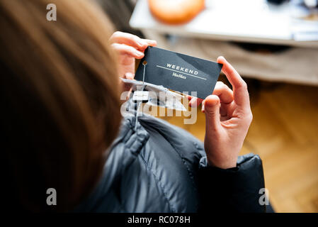 PARIS, FRANCE - FEB 2, 2018: Overhead view of woman wearing Max Mara Weekend Italian buy new fashionable down jacket reading price tag and logo - Stock Photo