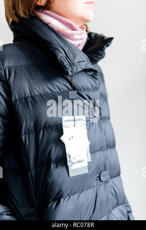 View from above of Woman wearing buy new fashionable down jacket with price tag and logo - Stock Photo