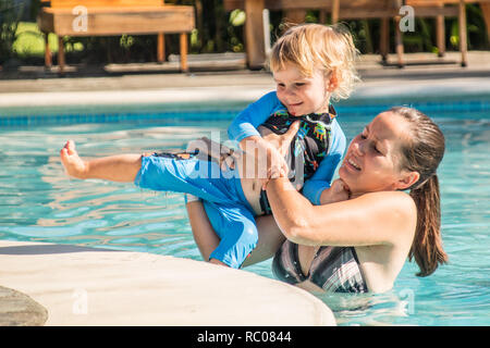 A happy boy and his mother getting out from the swimming pool - Stock Photo