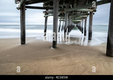 As the sun rises behind the Sandbridge Fishing Pier, the waves crash underneath --themes: perspective, peace, long exposure, slow shutter, misty - Stock Photo