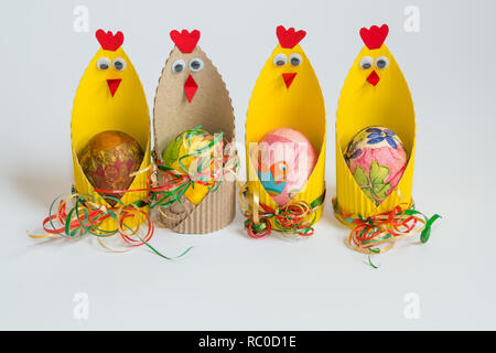 Easter decoration with colorful eggs in hand made paper chicks isolated on white background. - Stock Photo