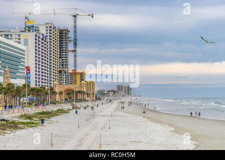 19 December 2019 - Daytona Beach, Florida, USA. People enjoy colourful buildings and a white sand beach in the sunset. - Stock Photo