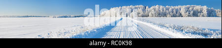 beautiful winter landscape panorama with road and forest. panoramic view of snow covered forest and field - Stock Photo