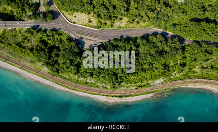 Aerial stock photo of car driving along the winding mountain pass road through the forest in Sochi, Russia. People traveling, road trip on curvy road - Stock Photo