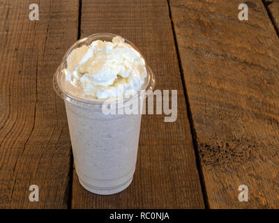 Vanilla Frappe coffee drink in a clear cup with whipped cream on top on a barn wood background with copy space. - Stock Photo