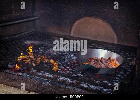 Cooking traditional chicken feet and meet sausage on a coal grill in South African reastaurant - Stock Photo
