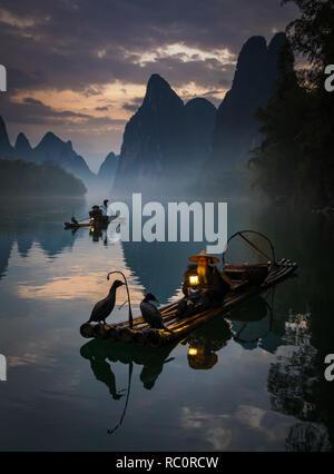 Cormorant fisherman and his birds on the Li River in Yangshuo, Guangxi, China - Stock Photo