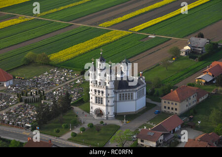 Aerial view of Holy Trinity Church in a small European village in sunset, a cemetery next to the church, unique architecture, Odranci, Slovenia - Stock Photo