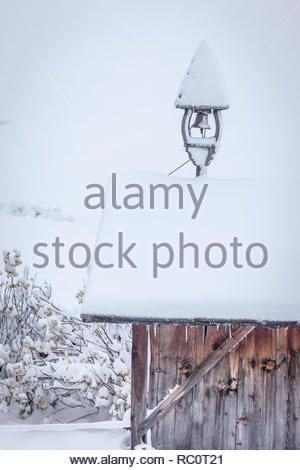 Snowy belfry on a hut at a farm in Riva di Tures, South Tyrol, Italy - Stock Photo