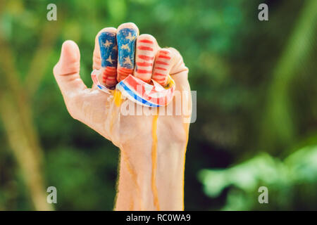 The USA hand squeezes the North Korean egg. Conflict between the United States and North Korea. - Stock Photo