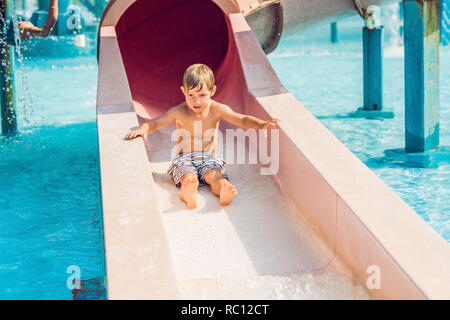 The boy is having fun in the water park. - Stock Photo