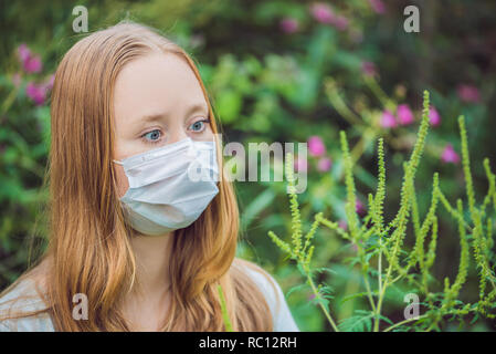 Young woman in a medical mask because of an allergy to ragweed. - Stock Photo