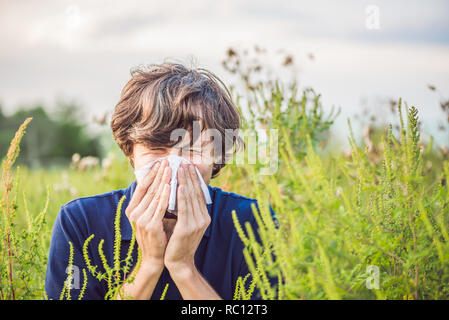 Young man sneezes because of an allergy to ragweed. - Stock Photo