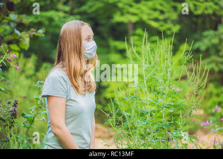 Young woman in a medical mask because of an allergy to ragweed - Stock Photo