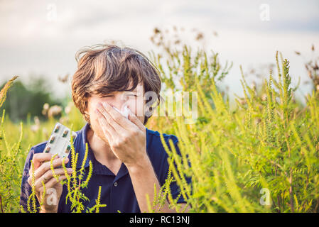 Young man sneezes because of an allergy to ragweed - Stock Photo