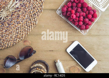 Summer holiday, vacation, relaxation concept. Raspberries, straw hat, smartphone, sunglasses from above, top view, flat lay on wooden background. Free text copy space. Summer vibes concept. - Stock Photo