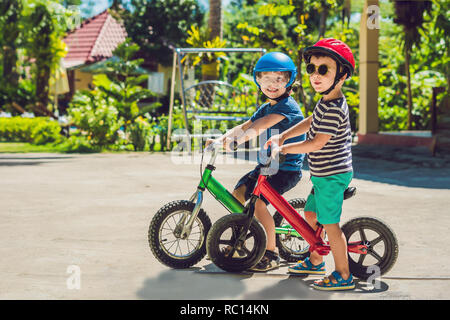 Two little boys children having fun on Balance Bike on a country tropical road - Stock Photo