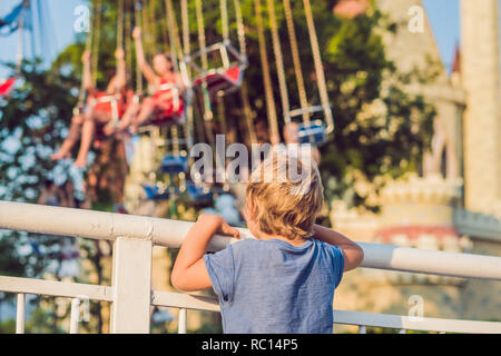 The boy wants to ride on the merry-go-round - Stock Photo